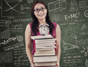 Asian female student bring stack of books in class
