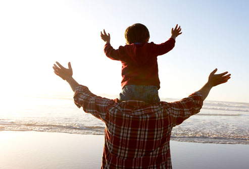 child sitting on father's shoulders with hands uplifted